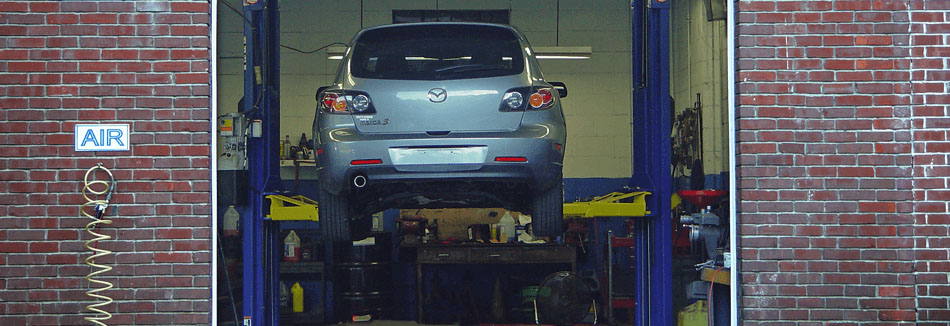 Inside a service bay at Tony's Garage, where an SUV is on a lift getting serviced.